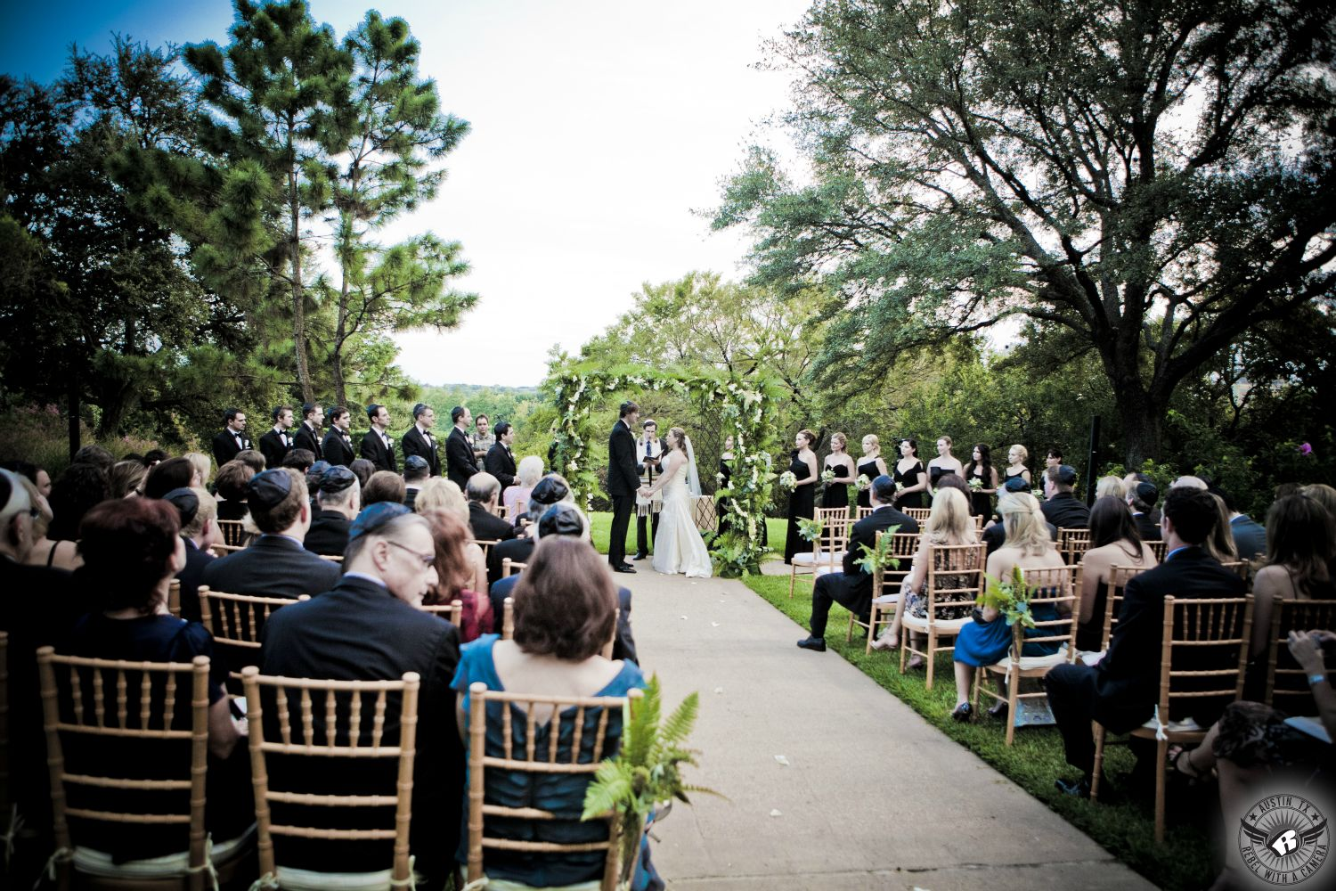 Elegant Outdoor Jewish Wedding Ceremony With Golden Chiavari Chairs Hanging Ferns And Wrought Iron Chuppah