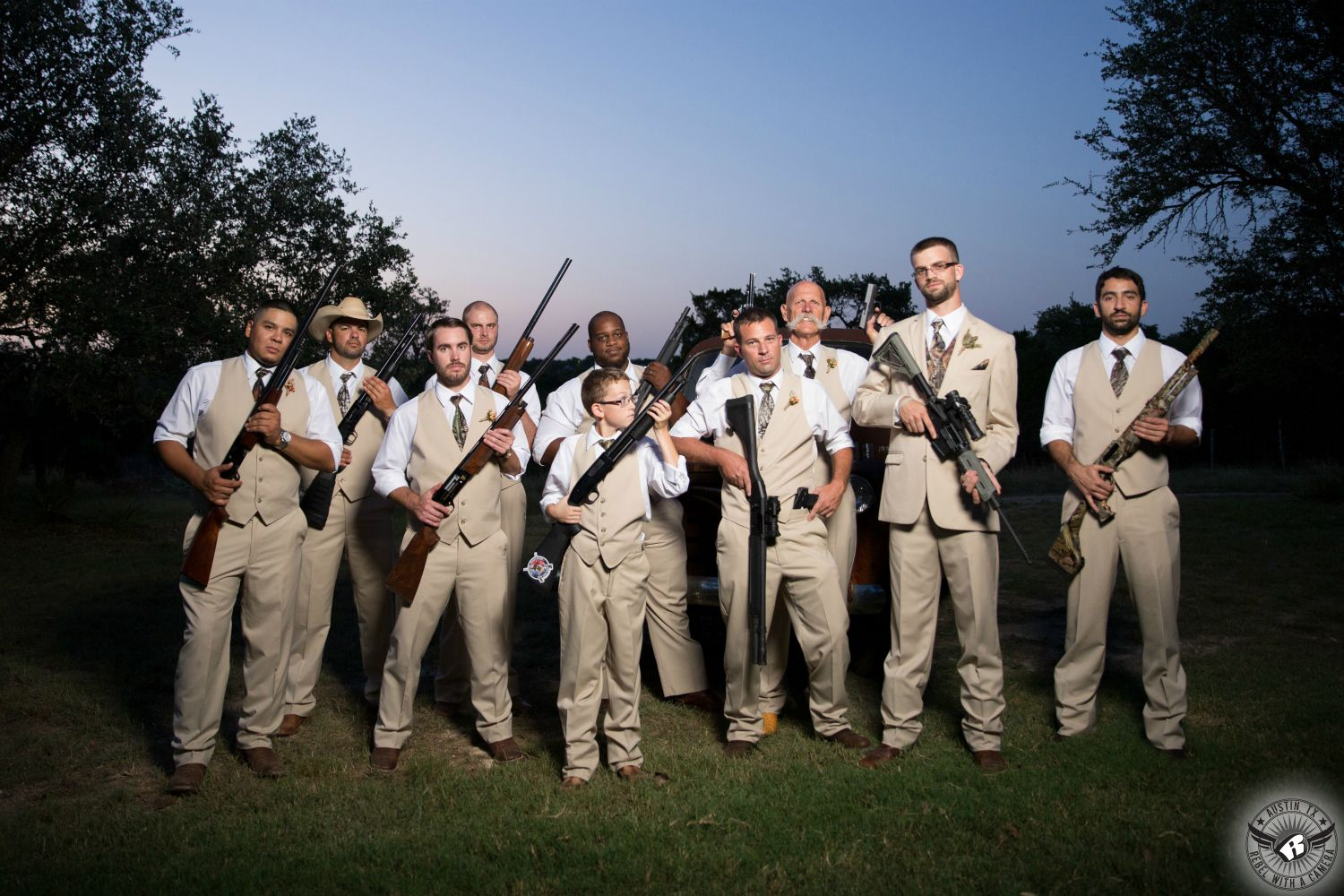 wedding photo of groom and groomsmen in beige suits with camo vests and ties hold rifles