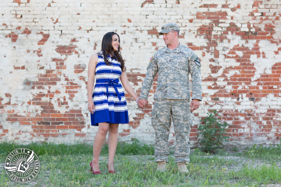 Army engagement pictures in Texas soldier and bride in front of brick wall