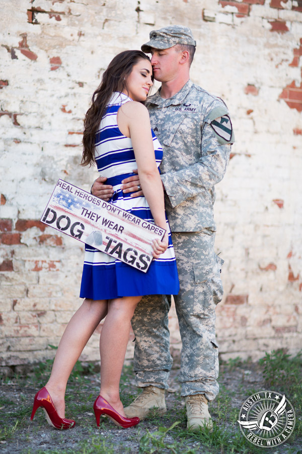 Army engagement pictures in Texas soldier and bride embrace in front of brick wall