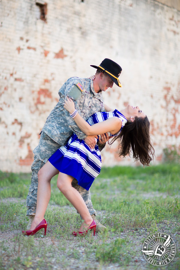 Army engagement pictures in Texas soldier dips bride in front of brick wall