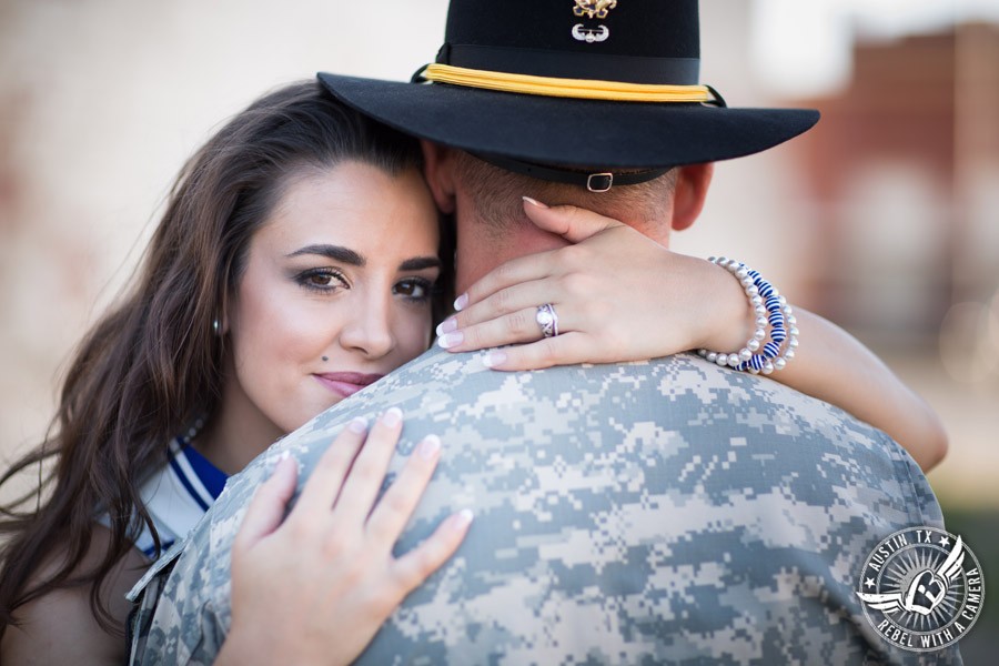 Army engagement pictures in Texas soldier and bride looks over his shoulder