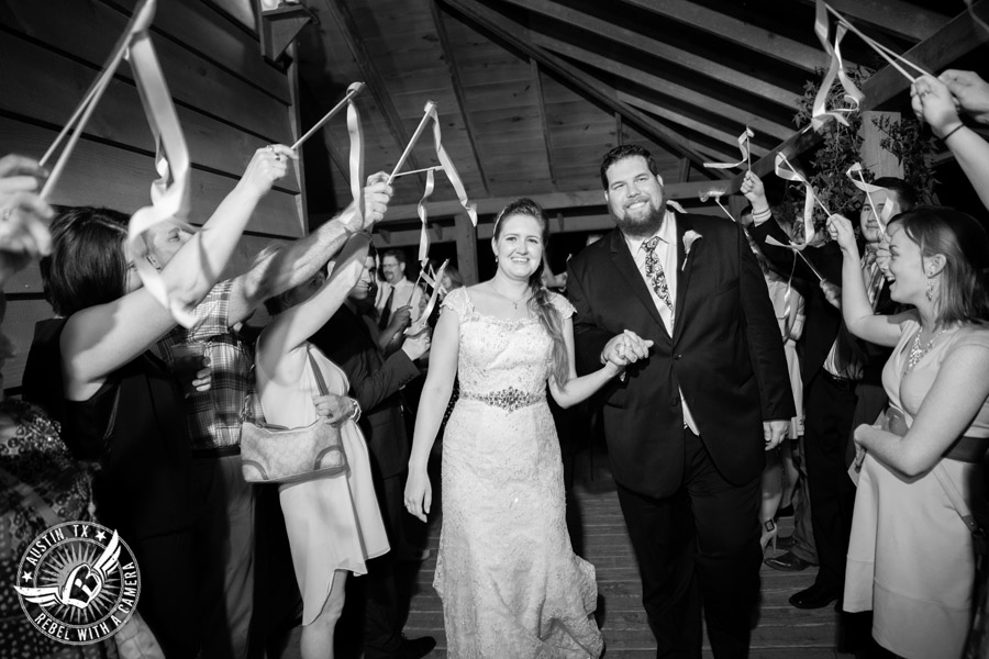 Sage Hall wedding photos at Texas Old Town happy bride and groom exit the reception while guests wave ribbon wands