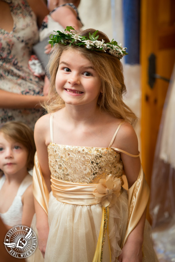 Picture of flower girl in golden, sparkly dress and flower crown in a wedding at the Driskill Hotel in Austin, Texas