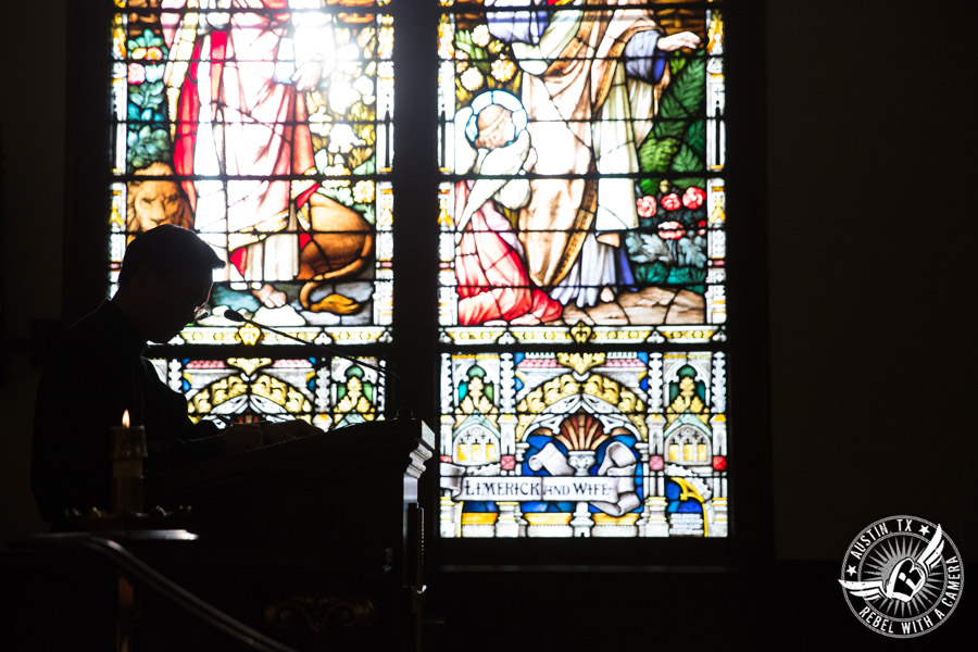 Picture of reader and stained glass window at wedding ceremony at St. Mary Cathedral in Austin, Texas
