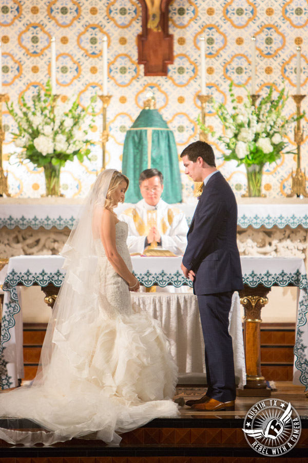 Picture of bride and groom praying during wedding ceremony at St. Mary Cathedral in Austin, Texas
