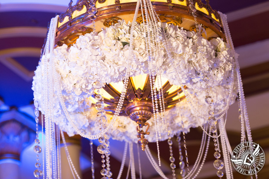 Picture of white floral piece for chandelier with gold, crystal, and pearl accents at wedding reception at Driskill Hotel mezzanine with florals by Flora Fetish