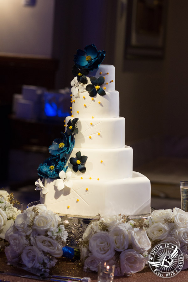 Picture of 5-tiered white fondant wedding cake with blue and yellow gum paste flowers at the Driskill Hotel in Austin, Texas
