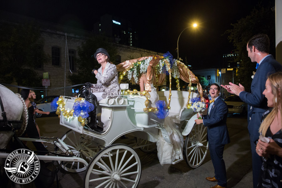 Picture of bride and groom exiting wedding reception and taking a carriage ride in front of the Driskill Hotel in Austin, Texas
