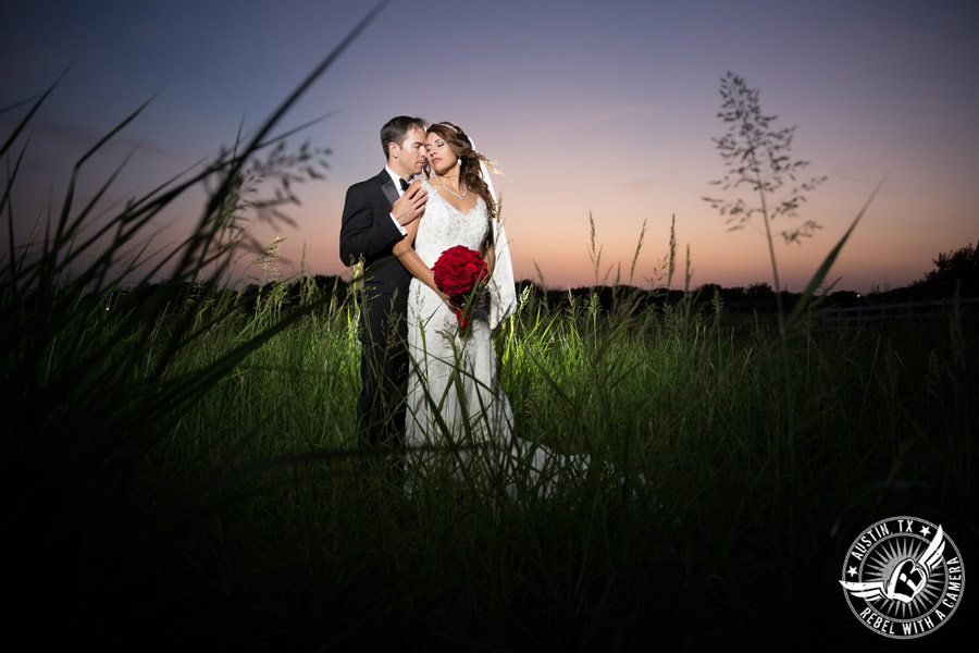 Taylor Mansion wedding photo of bride and groom in field at sunset with red rose bouquet