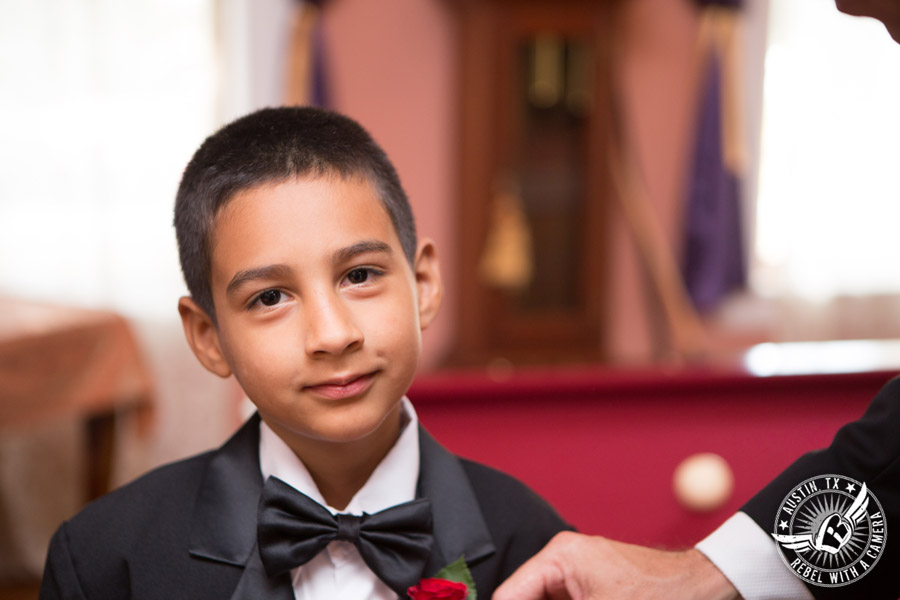 Taylor Mansion wedding photo groom pins boutonniere on ring bearer in groom's room