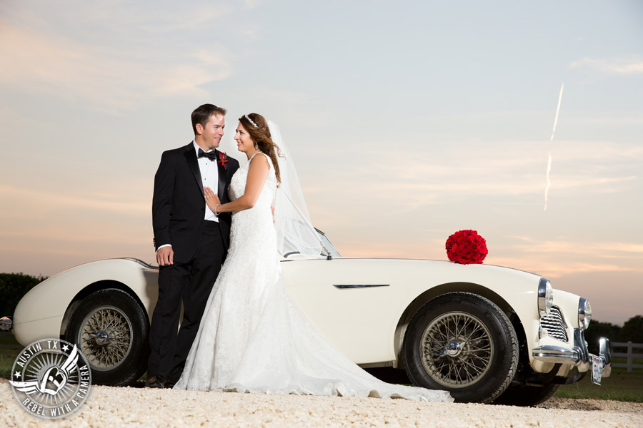 Taylor Mansion wedding photo of bride and groom with white convertible and red rose bouquet
