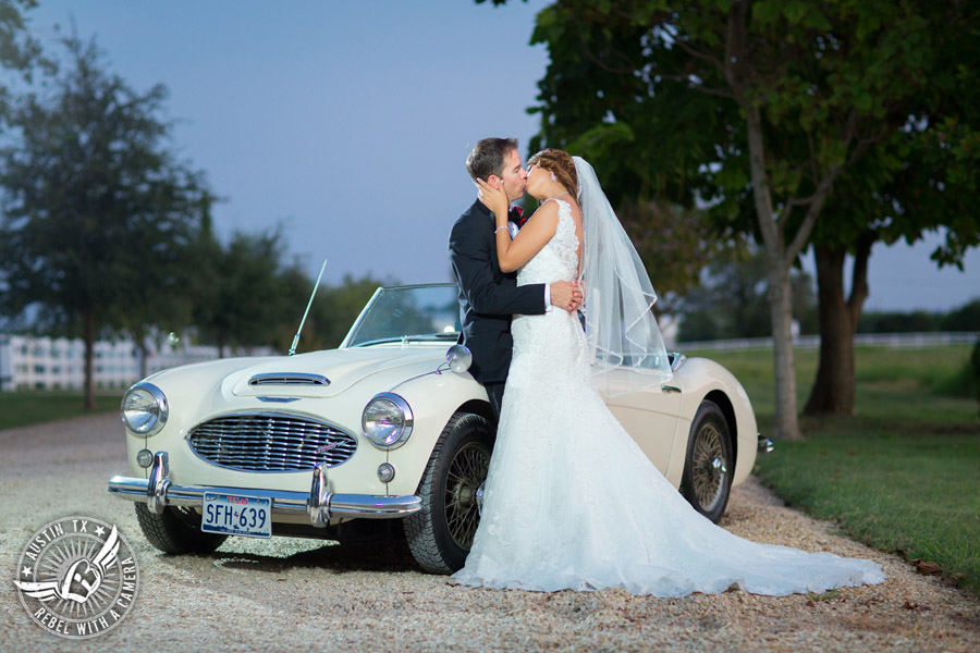 Taylor Mansion wedding photo of bride and groom kissing with white convertible