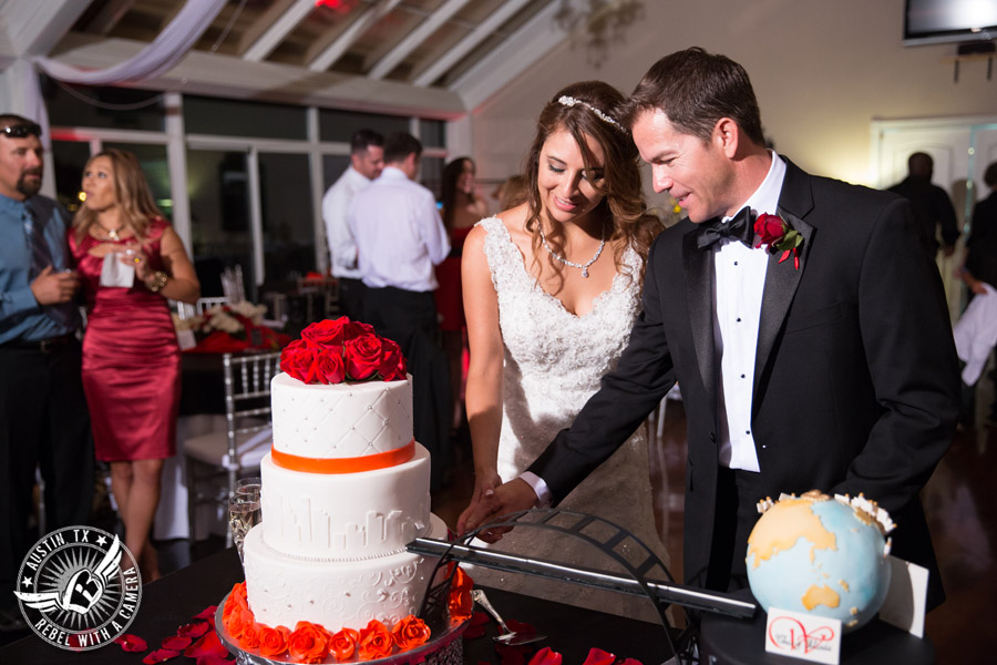 Taylor Mansion wedding photo bride and groom cut bride's cake with red roses and travel globe groom's cake by Sweet Life of Cakes