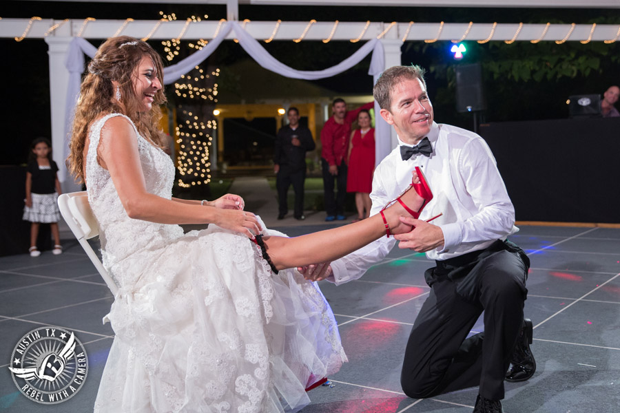 Taylor Mansion wedding photo groom takes garter off bride on the patio with 1st Class Entertainment DJ Jason