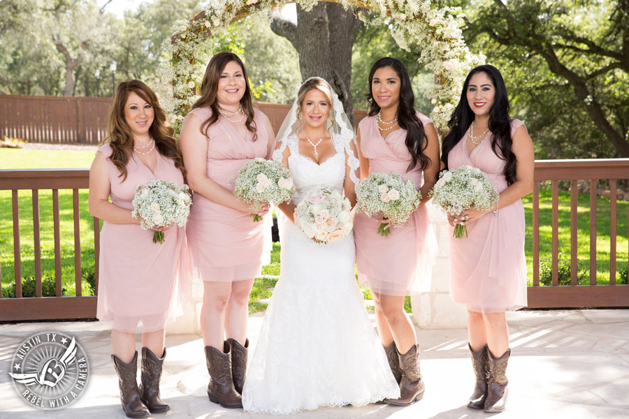 Romantic wedding pictures at The Springs Events in Georgetown, Texas - Gabriel Springs - happy bride and bridesmaids in light pink dresses and brown cowboy boots