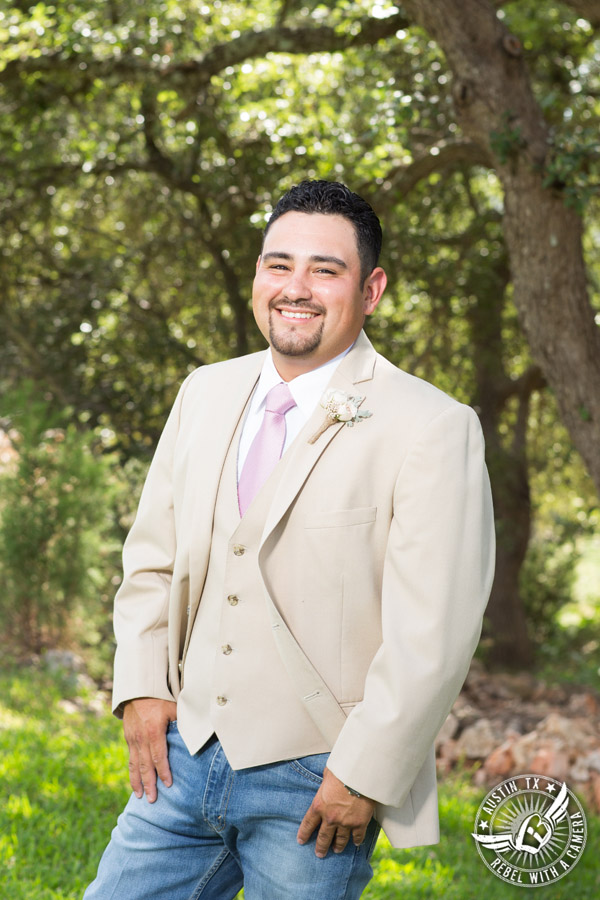 Romantic wedding pictures at The Springs Events in Georgetown, Texas - Gabriel Springs - happy groom in tan vest and jacket with light pink tie