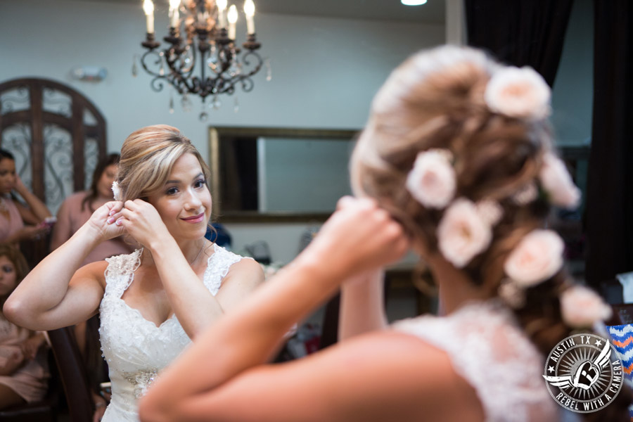 Romantic wedding pictures at The Springs Events in Georgetown, Texas - Gabriel Springs - bride puts on earrings in the bride's room