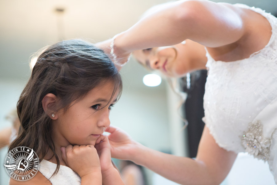 Romantic wedding pictures at The Springs Events in Georgetown, Texas - Gabriel Springs - bride puts on flower girl's earrings in the bride's room