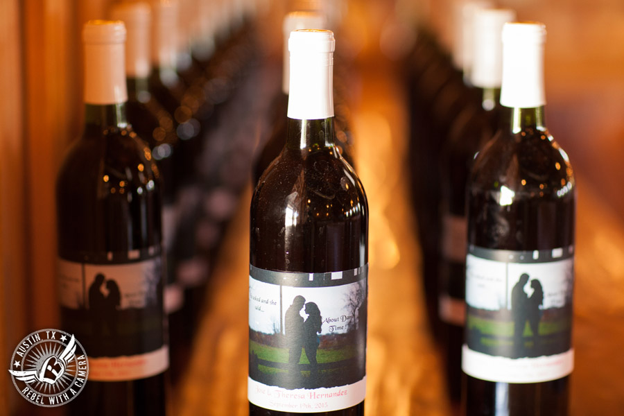 Romantic wedding pictures at The Springs Events in Georgetown, Texas - Gabriel Springs - customized wine bottles for guest favors with engagement picture on label