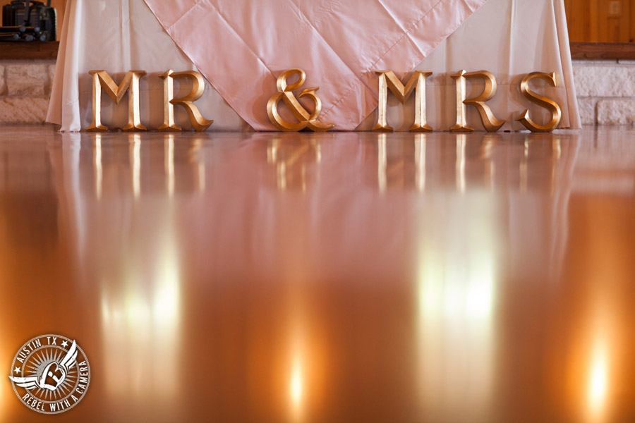 Romantic wedding pictures at The Springs Events in Georgetown, Texas - Gabriel Springs - gold Mr. and Mrs. signage at head table at the reception with light pink table linens