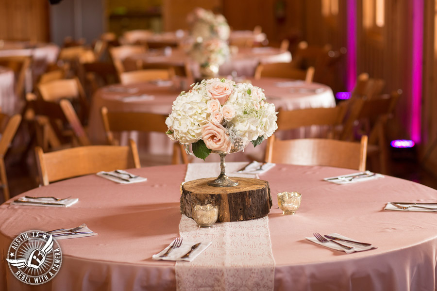 Romantic wedding pictures at The Springs Events in Georgetown, Texas - Gabriel Springs - light pink rose and white hydrangea floral centerpieces on wood log stand by Sixpence Floral Design with light pink linens and lace table runner