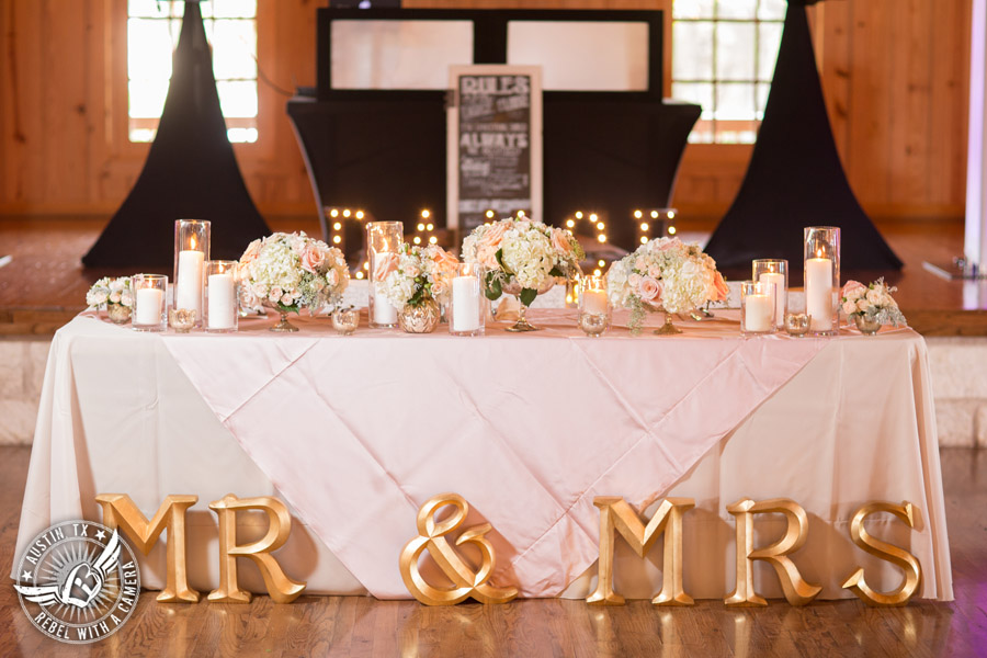 Romantic wedding pictures at The Springs Events in Georgetown, Texas - Gabriel Springs - gold Mr. and Mrs. signage at head table at the reception with light pink table linens with rose floral centerpieces and candles by Sixpence Floral Design
