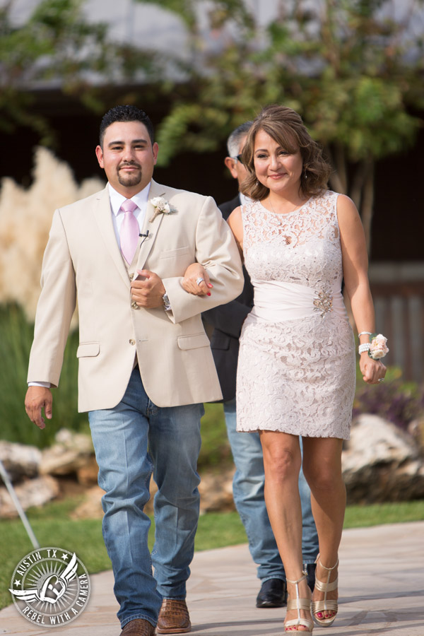 Romantic wedding pictures at The Springs Events in Georgetown, Texas - Gabriel Springs - groom in tan jacket with light pink tie escorts mother in short lace dress down the aisle