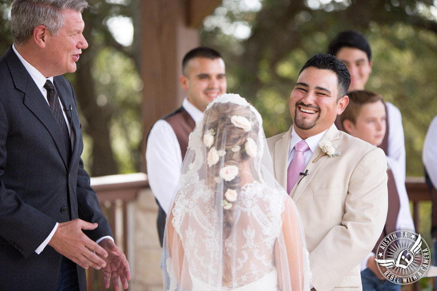 Romantic wedding pictures at The Springs Events in Georgetown, Texas - Gabriel Springs - groom smiles at bride as they hold hands during the wedding ceremony