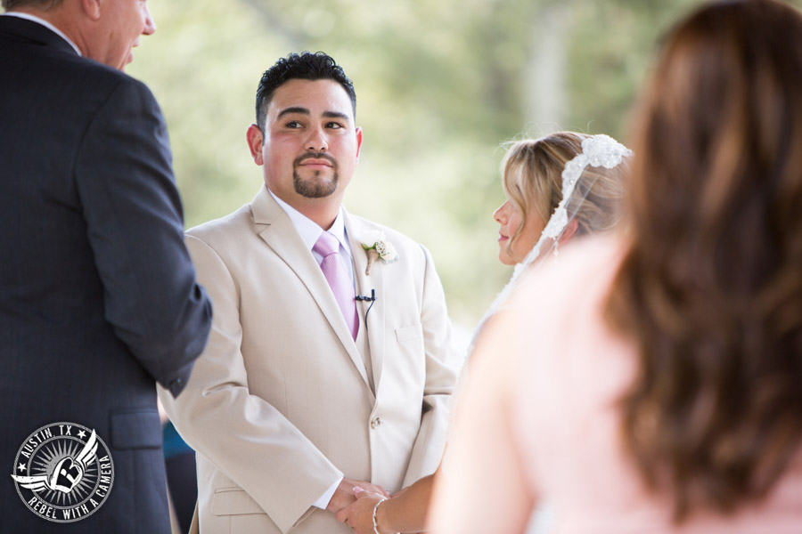 Romantic wedding pictures at The Springs Events in Georgetown, Texas - Gabriel Springs - groom looks at officiant as he holds hands with the bride during the wedding ceremony