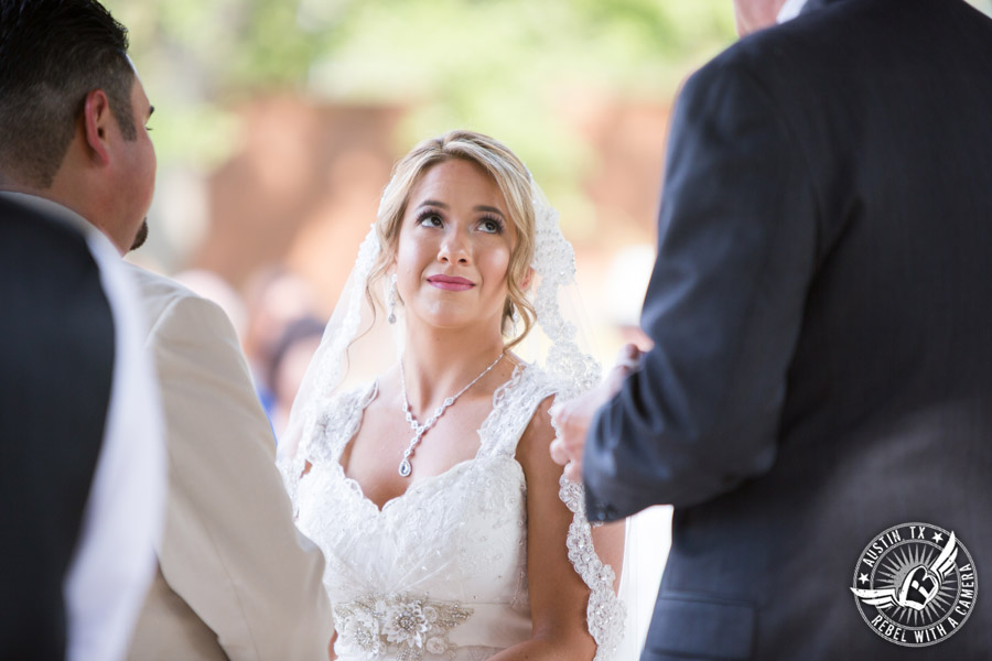 Romantic wedding pictures at The Springs Events in Georgetown, Texas - Gabriel Springs - bride looks at officiant as she holds hands with the groom during the wedding ceremony