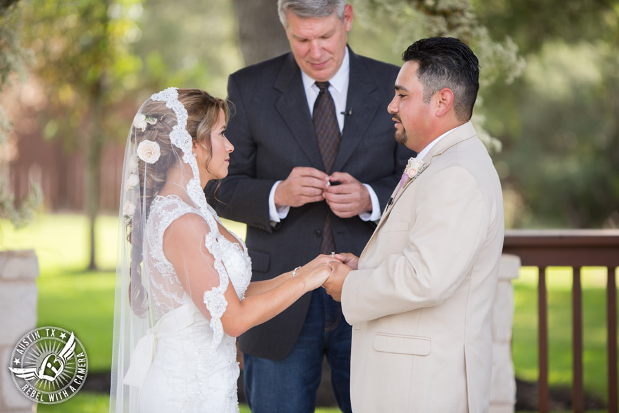 Romantic wedding pictures at The Springs Events in Georgetown, Texas - Gabriel Springs - bride and groom hold hands during the wedding ceremony