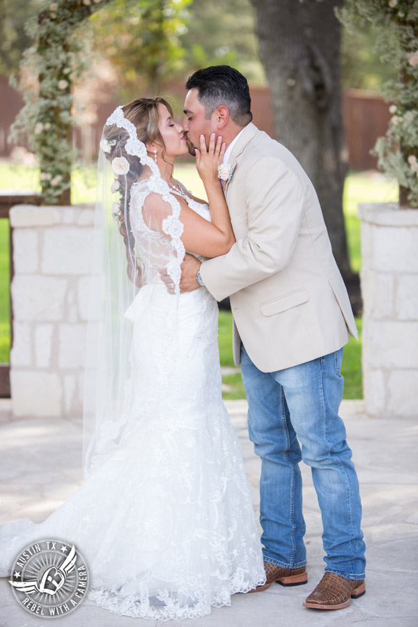 Romantic wedding pictures at The Springs Events in Georgetown, Texas - Gabriel Springs - bride and groom kiss at the end of the wedding ceremony