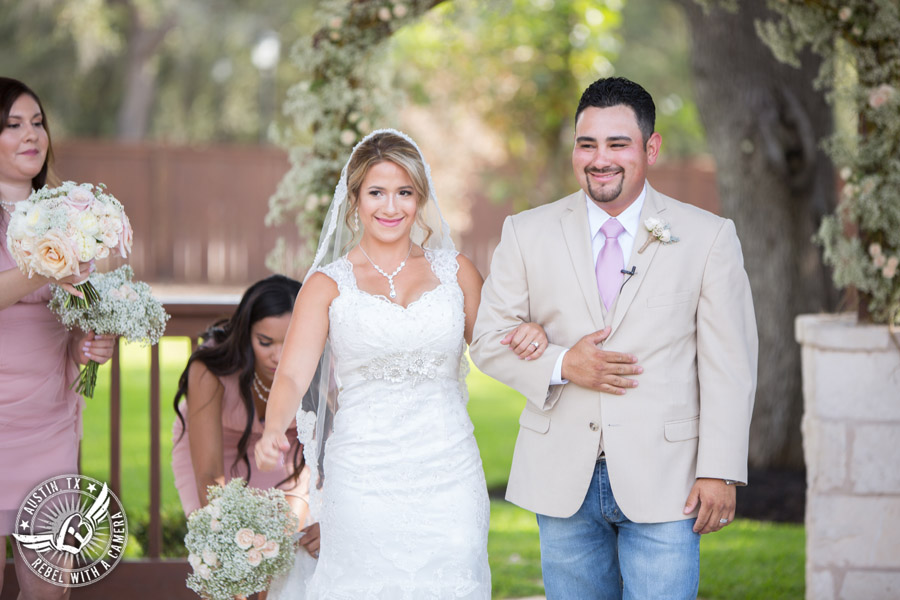 Romantic wedding pictures at The Springs Events in Georgetown, Texas - Gabriel Springs - bride and groom walk down the aisle as husband and wife at the end of the wedding ceremony