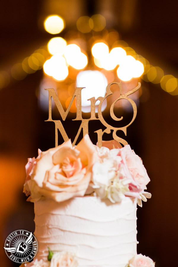 Romantic wedding pictures at The Springs Events in Georgetown, Texas - Gabriel Springs - five tiered white buttercream wedding cake with light pink roses and gold Mr. and Mrs. cake topper by Classy Cakes by Lori