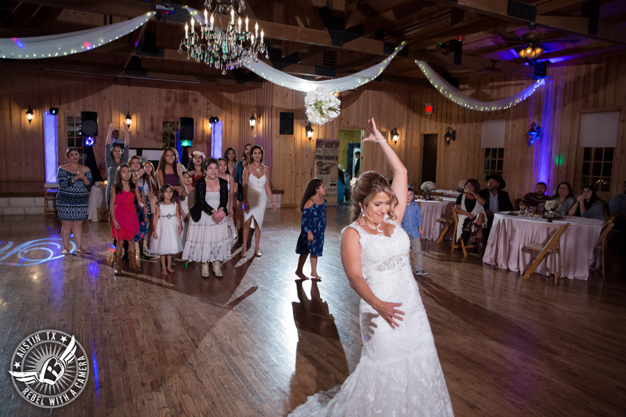 Romantic wedding pictures at The Springs Events in Georgetown, Texas - Gabriel Springs - bride throws the bouquet during the wedding reception with Made from Scratch Weddings DJ