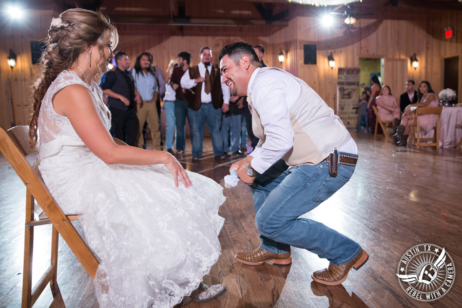 Romantic wedding pictures at The Springs Events in Georgetown, Texas - Gabriel Springs - groom takes off the bride's garter during the wedding reception with Made from Scratch Weddings DJ