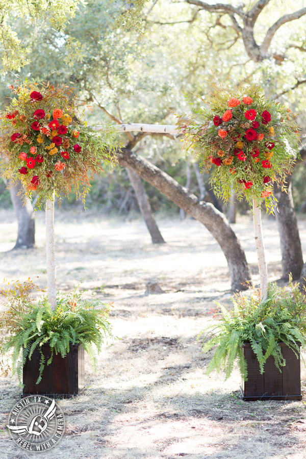 Hamilton Twelve wedding photos - ceremony site birch bark arbor by the Flower Girl with red and orange roses and gerbera daisies