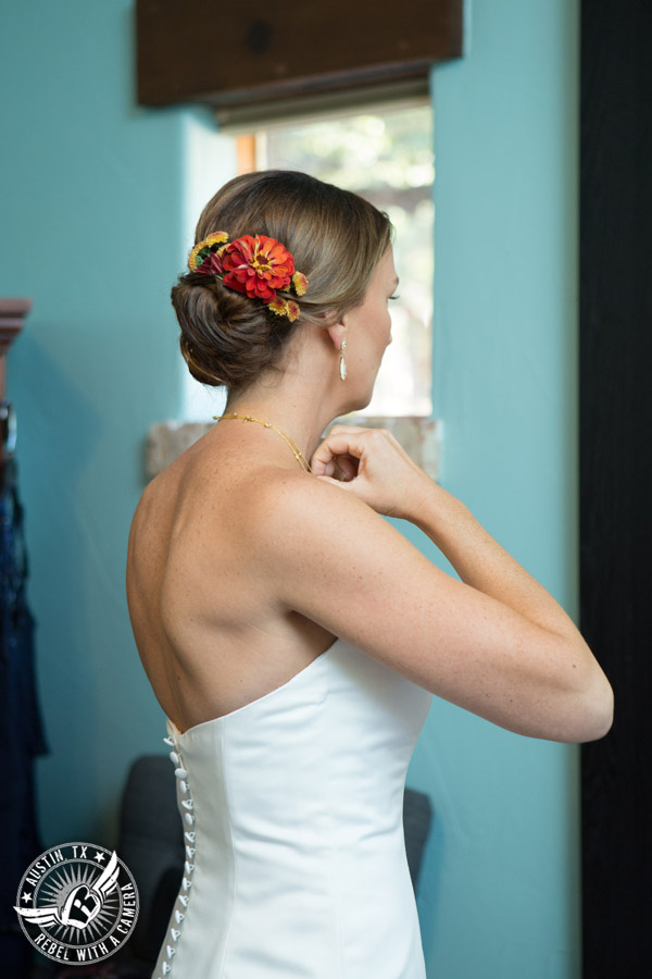 Hamilton Twelve wedding photos - bride straightens necklace in the bride's room - floral updo by Kiss by Katie