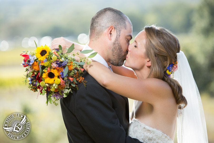 Wedding pictures at Thurman's Mansion at the Salt Lick - bride and groom kiss with colorful wildflower bouquet by Verbena Floral Design