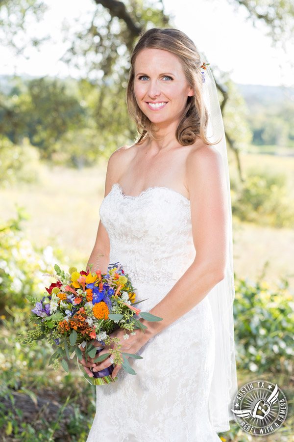 Wedding pictures at Thurman's Mansion at the Salt Lick - bride under the oak trees - colorful wildflower bridal bouquet by Verbena Floral Design - hair and makeup by Topaz Salon