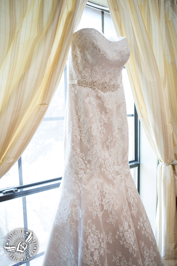 Wedding pictures at Thurman's Mansion at the Salt Lick - strapless lace bridal gown in the window in the bride's room