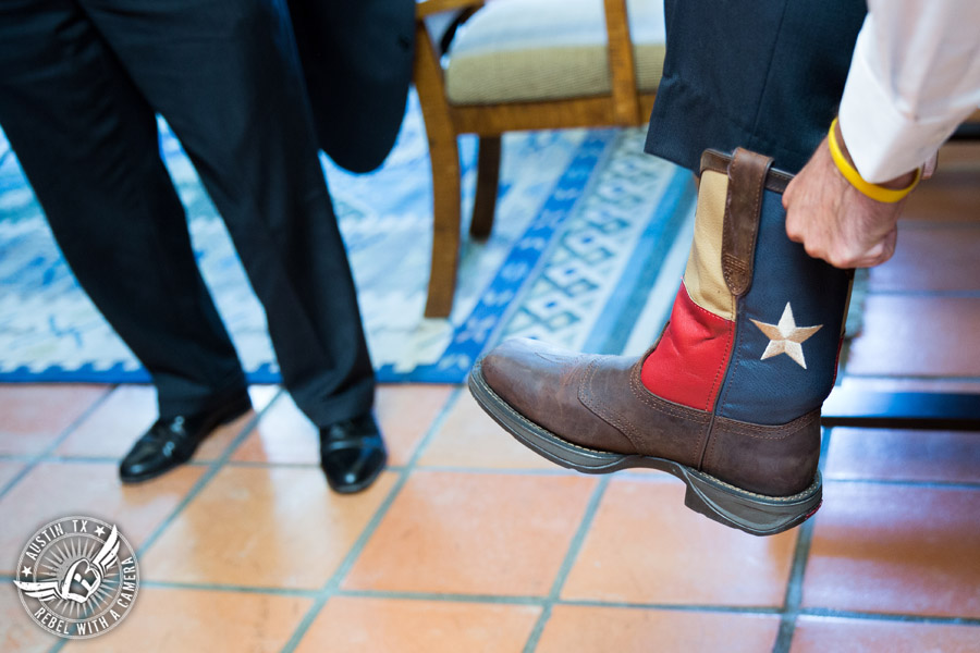 Wedding pictures at Thurman's Mansion at the Salt Lick - groom puts on Texas flag boots