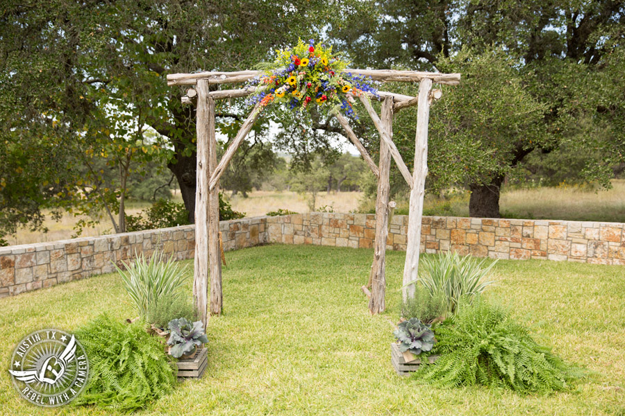 Wedding pictures at Thurman's Mansion at the Salt Lick - colorful wildflower arbor at the ceremony site by Verbena Floral Design