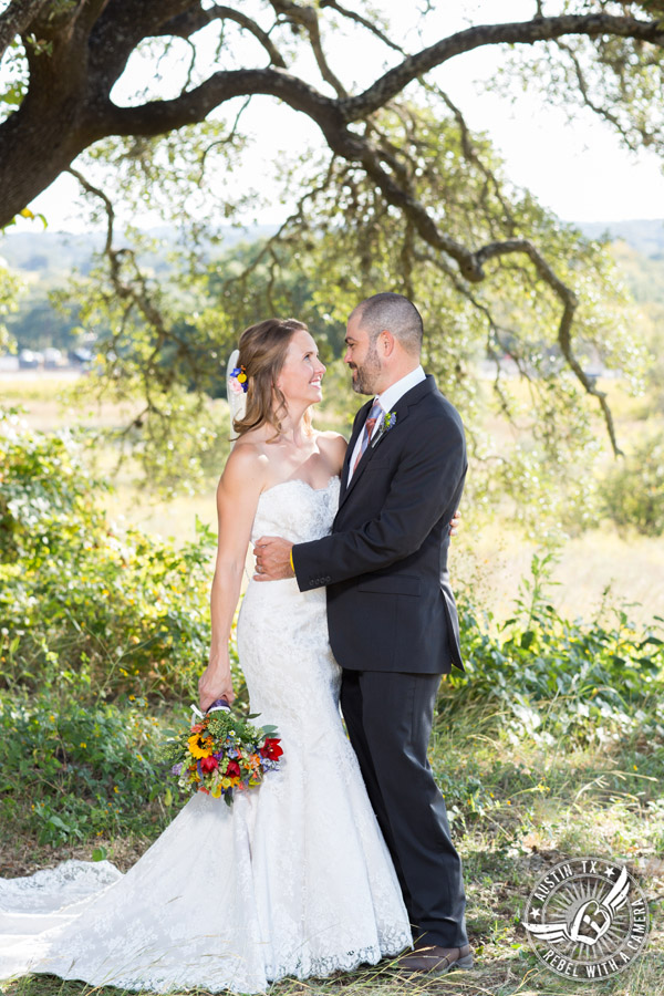 Wedding pictures at Thurman's Mansion at the Salt Lick - bride and groom look at each other under the oak trees