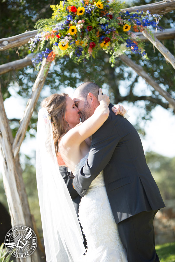 Wedding pictures at Thurman's Mansion at the Salt Lick - bride and groom kiss during the wedding ceremony