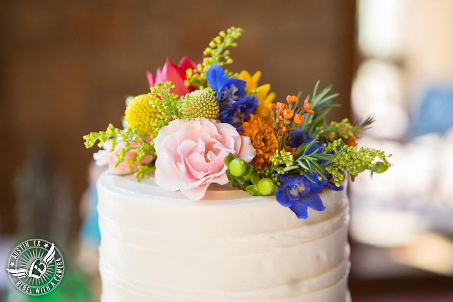 Wedding pictures at Thurman's Mansion at the Salt Lick - white buttercream bride's wedding cake Sweet Treets Bakery with colorful wildflowers by Verbena Floral Design