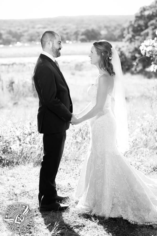 Wedding pictures at Thurman's Mansion at the Salt Lick - bride and groom hold hands in black and white