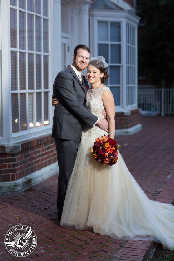 Wedding photo of happy bride and groom with bouquet by Bouquets of Austin outside at the Texas Federation of Women's Clubs Headquarters in Austin, Texas.