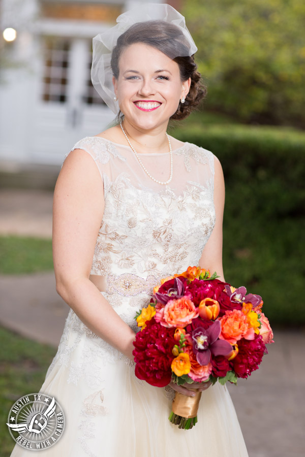 Wedding picture of happy bride with red and orange bouquet from Bouquets of Austin outside at the Texas Federation of Women's Clubs Headquarters in Austin, Texas